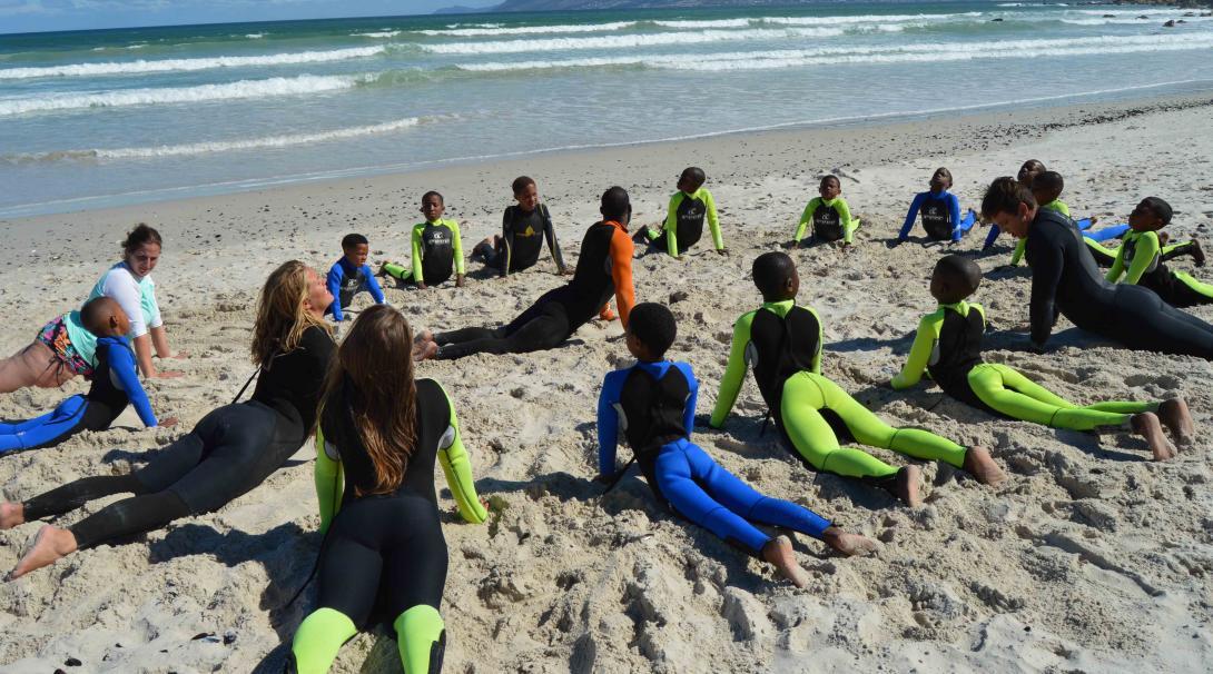 Voluntarios haciendo ejercicios de calentamiento antes de comenzar su voluntariado de Surf en Sudáfrica durante su año sabático.